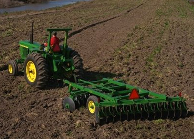225 Offset Disk being drawn behind a John Deere tractor