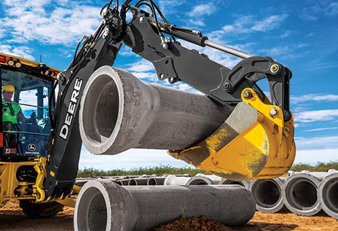 310SL HL Backhoe Loader moving storm sewer pipes with the backhoe