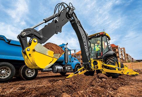 410L Backhoe Loader loading dirt into a dump truck with the backhoe