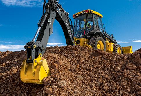 410L Backhoe Loader excavating dirt with the backhoe