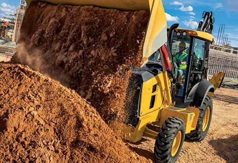 410L Backhoe Loader dumping sand from loader bucket at a construction ...