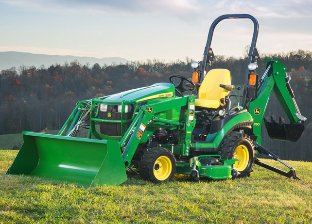 1025R Tractor Loader Backhoe in a grassy field with trees in the ...
