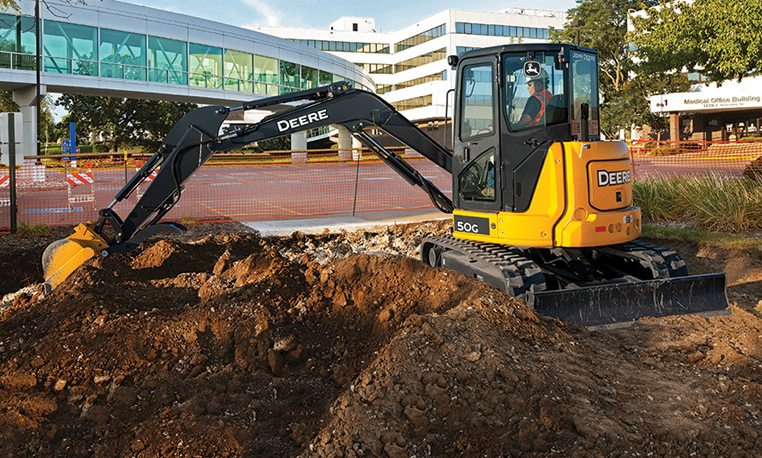 John Deere 50G Compact Excavator digging holes at construction site
