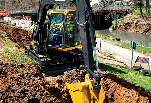 85G Excavator digging at a job site near a river