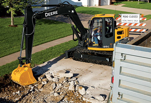 85G Excavator breaking up a road surface in front of a house in a ...