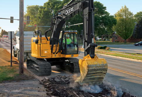 Man using a 245G LC Excavator to break apart a road surface during a ...