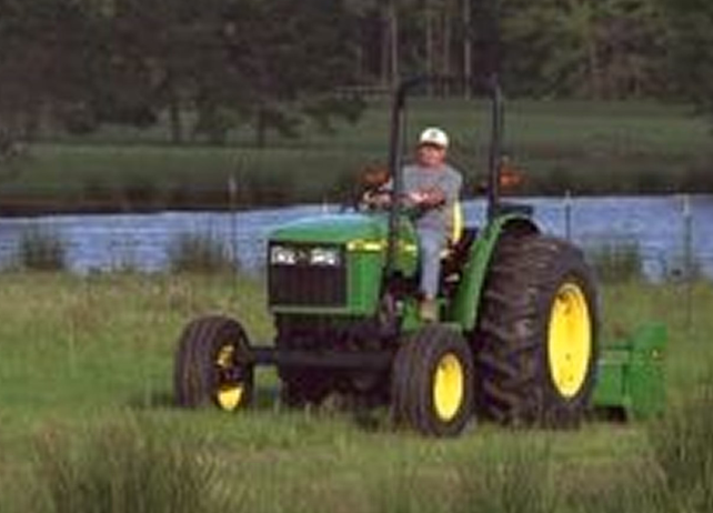 Man using a John Deere tractor with attached 370 Flail Mower to cut ...