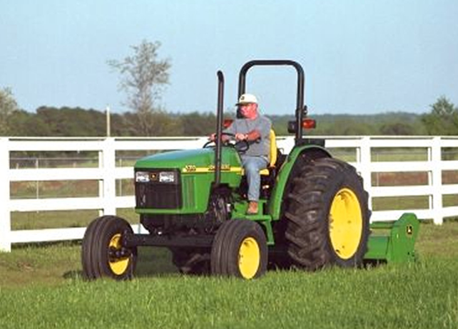 Man using a John Deere tractor with attached 390 Offset Flail Mower to ...