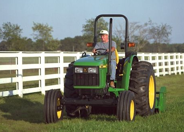 Man using a John Deere tractor with attached 25A Flail Mower to cut ...