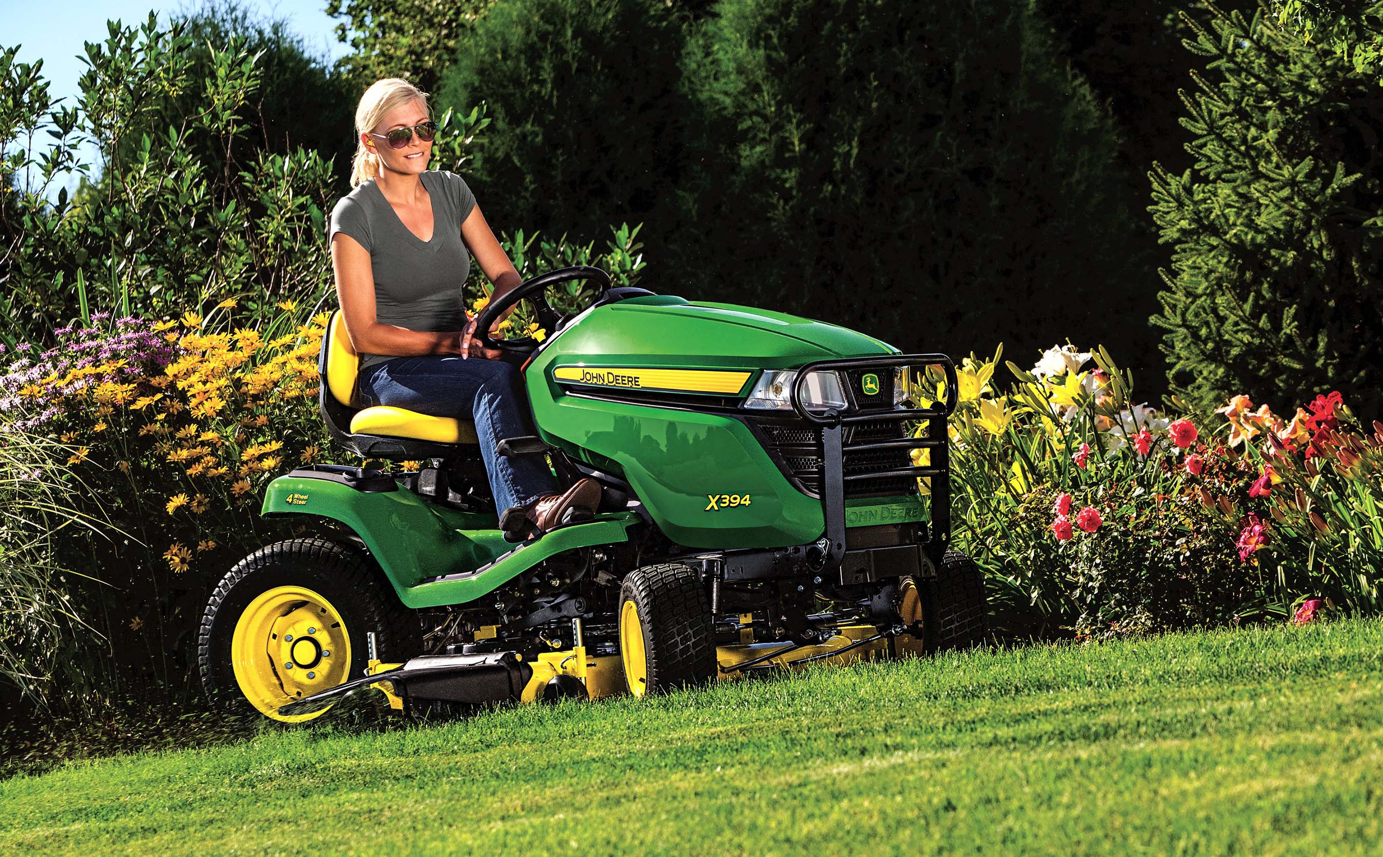 The John Deere X394 Select Series tractor mower has four-wheel ...