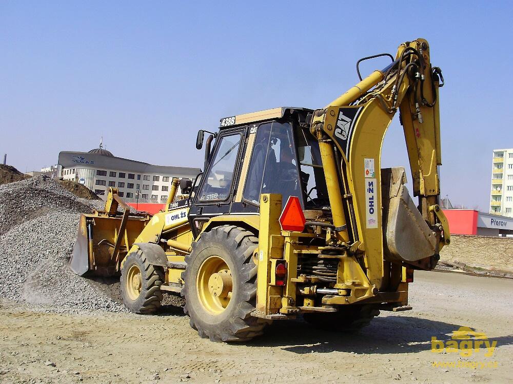 Rypadlo-nakladač Caterpillar 438B firmy OHL ŽS obhrnuje hromadu ...